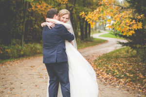 Bride and groom embracing each other on a country road