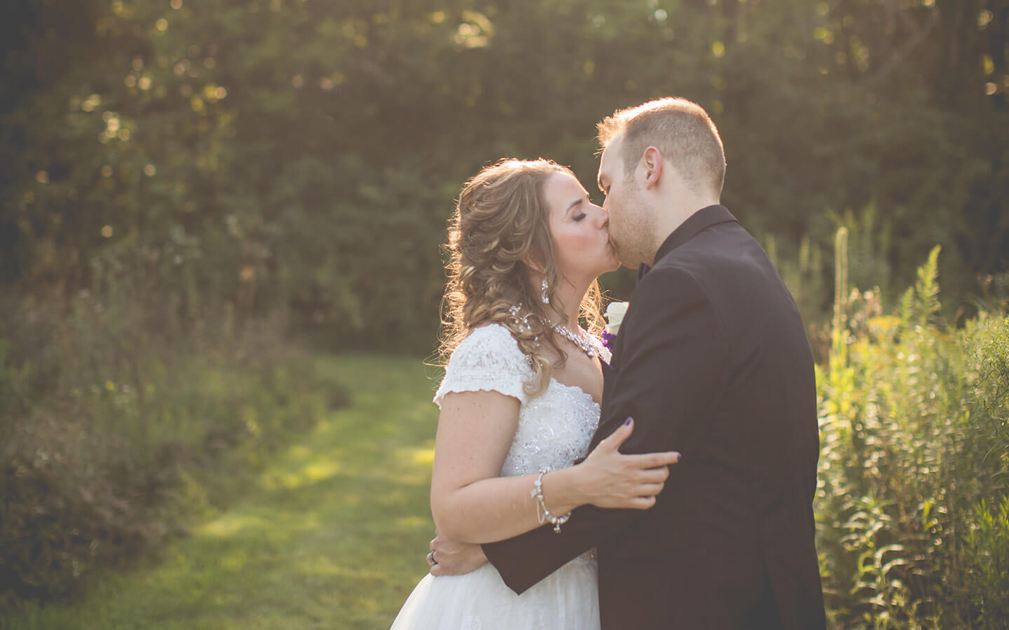 Bride and groom kissing on a sunny day at a destination wedding in Michigan