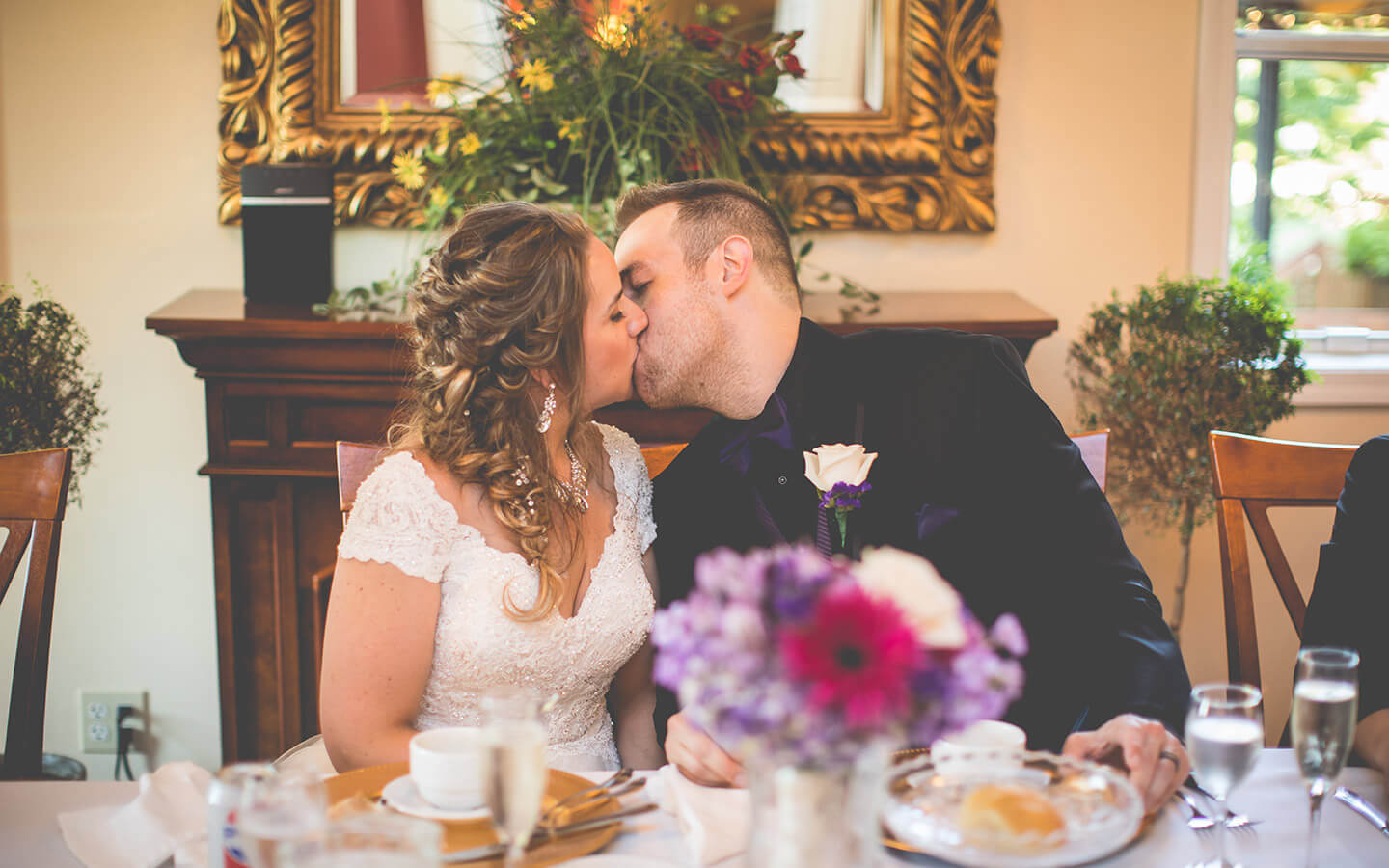 Destination wedding in Michigan, Bride and groom kissing at their reception table