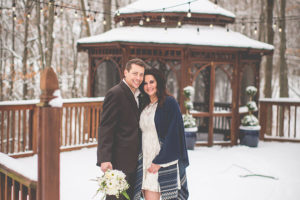 Bride and groom standing in front of a snowy gazebo