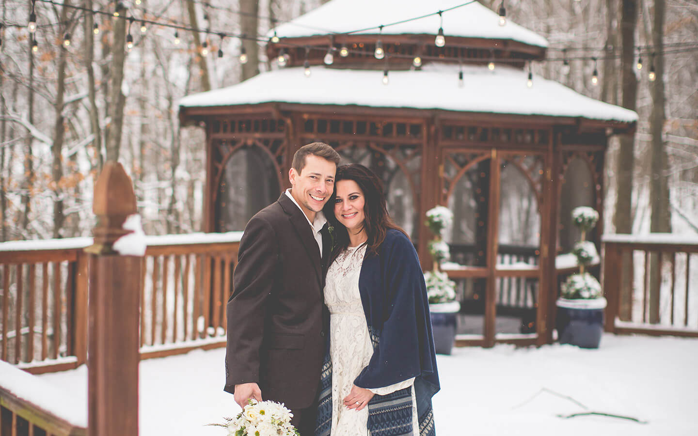 Bride and groom in front of a snowy gazebo at a Michigan Wedding in the winter