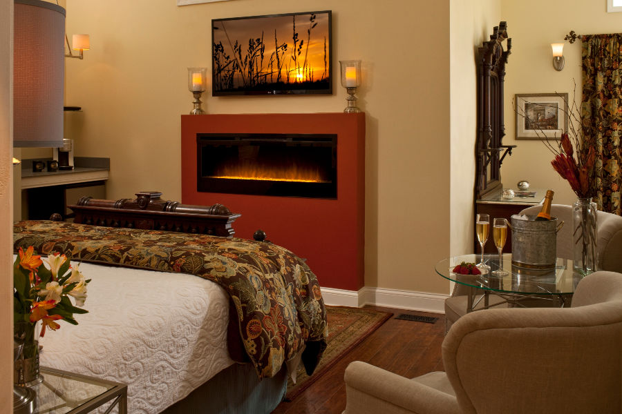 Michigan Honeymoon room - bed, fireplace, chairs, table with champagne on it