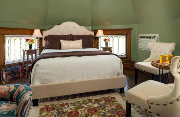 Room with a queen size bed with two widows and lamps on each side eight sided turret ceiling.
