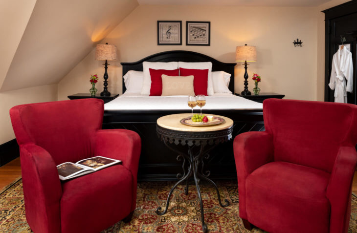 Room with a king size bed and seating area.