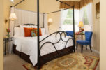 Room with a king size canopy bed side table and seating area