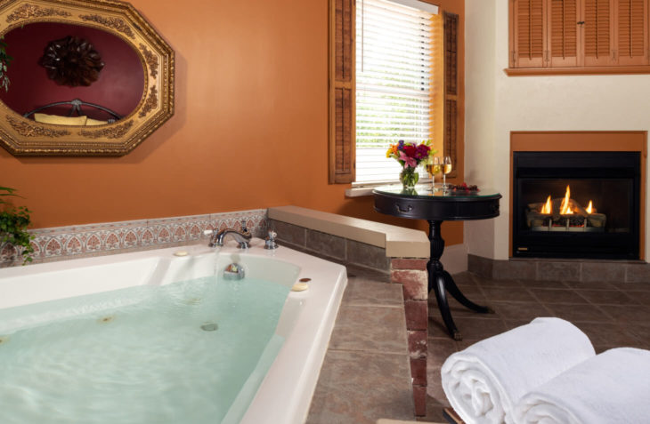 Two person whirlpool tub with a view of the fireplace.
