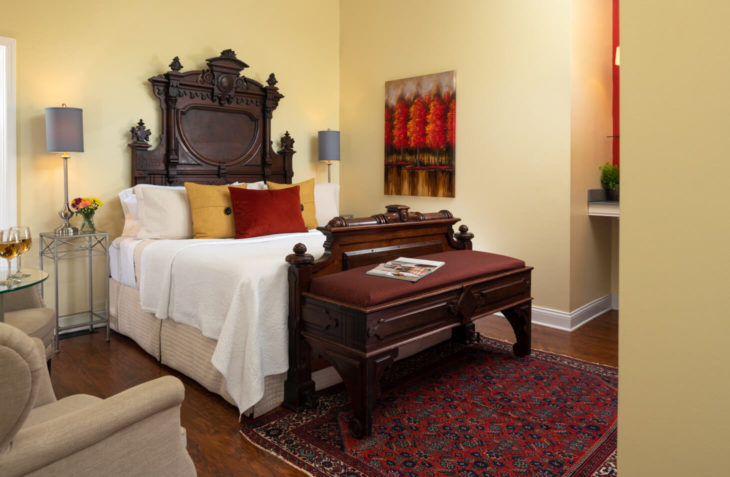 Room with a King size bed, seating area and bench with furnishings