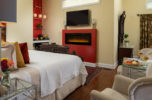 king size bed with large fireplace and television as well as seating area.