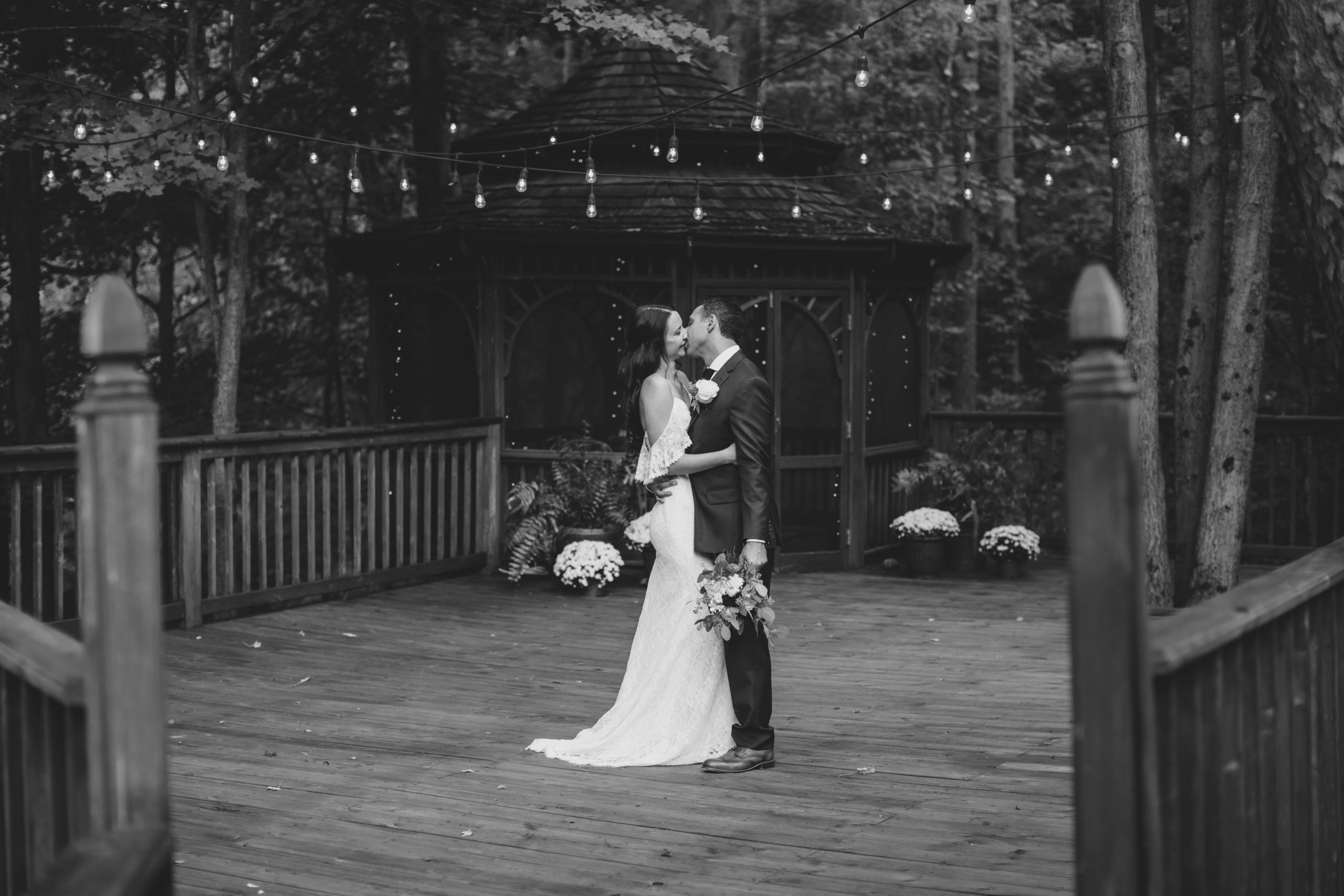 wedding couple on deck by gazebo with string lights and lush green trees surrounding them