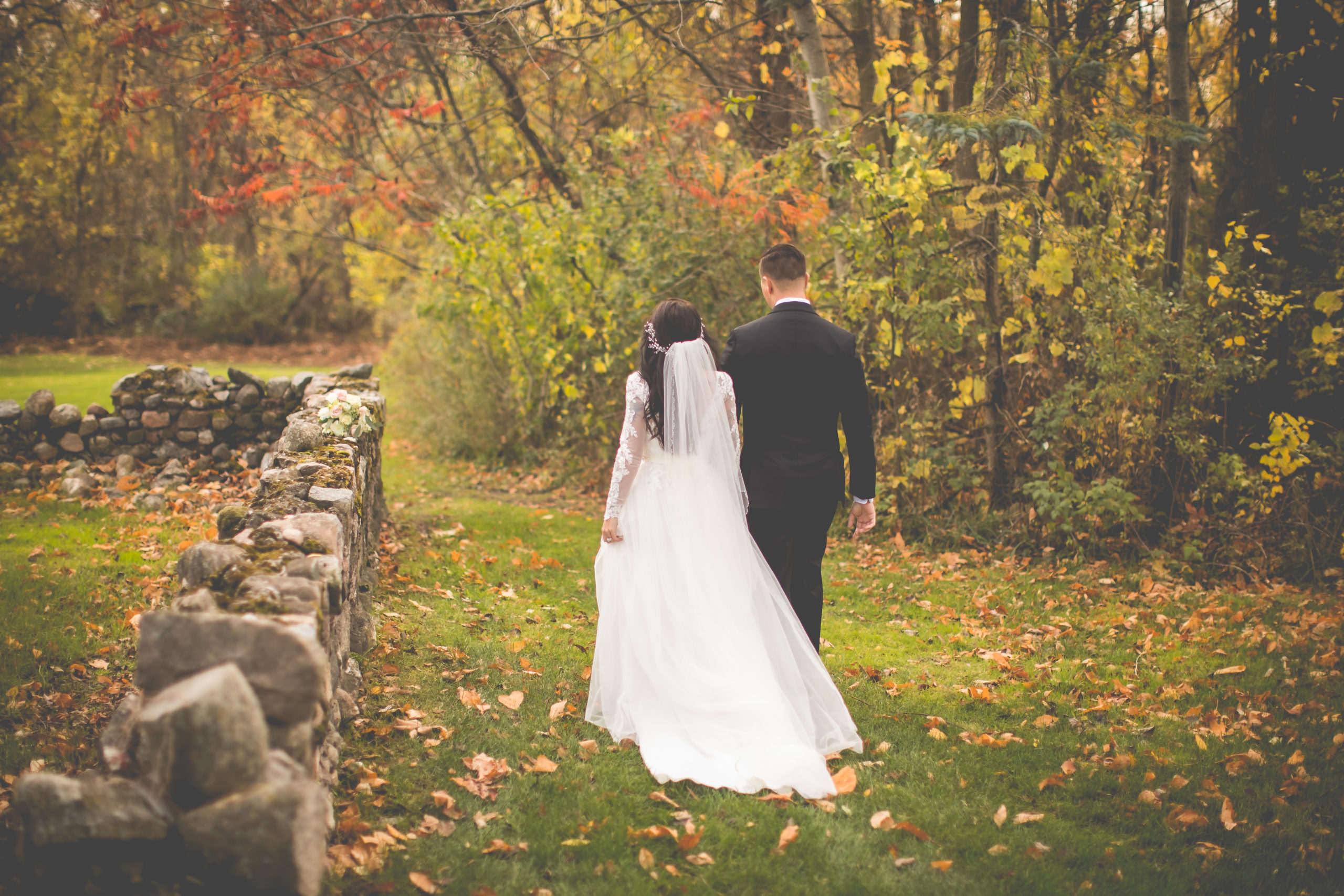 Bride & groom walking through the green grass surrounded by fall foliage and fallen leaves