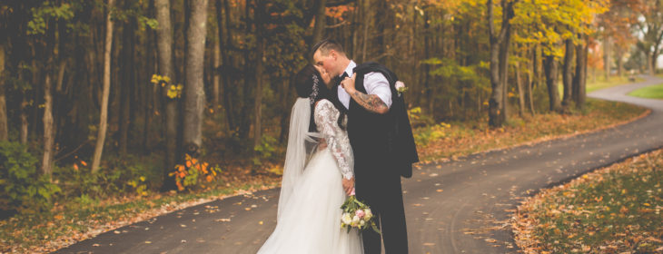Groom and bride kissing in the middle of The Castle drive surrounded by fall foliage