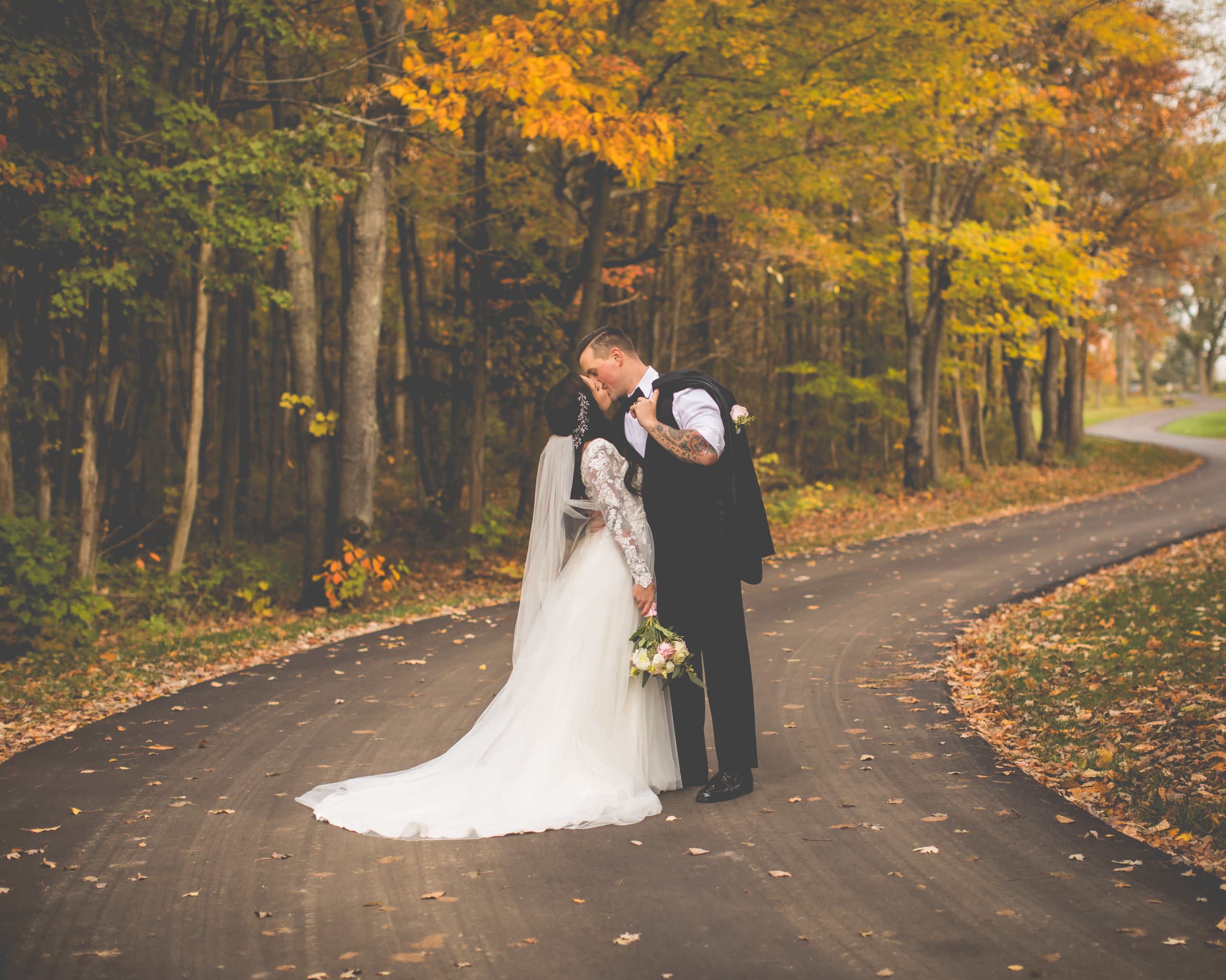 Groom & bride kissing in the middle of The Castle's curvy drive surrounded by fall foliage