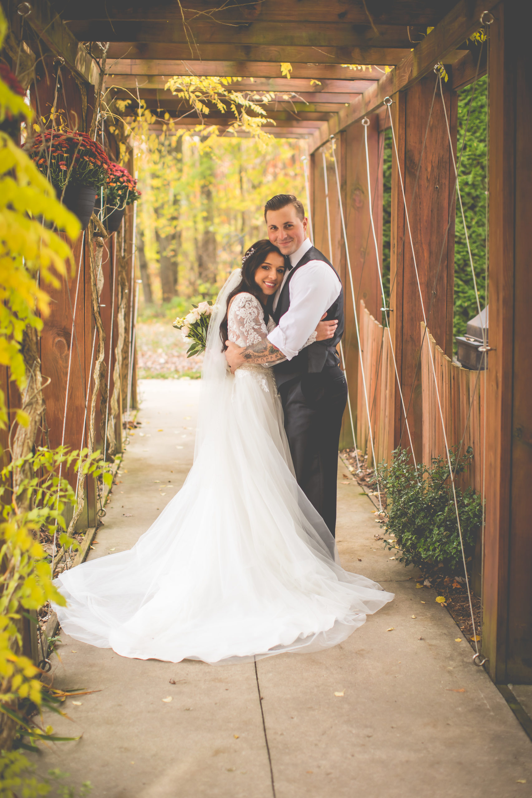 Bride and groom standing on a walkway outside surrounded by lush fall foliage