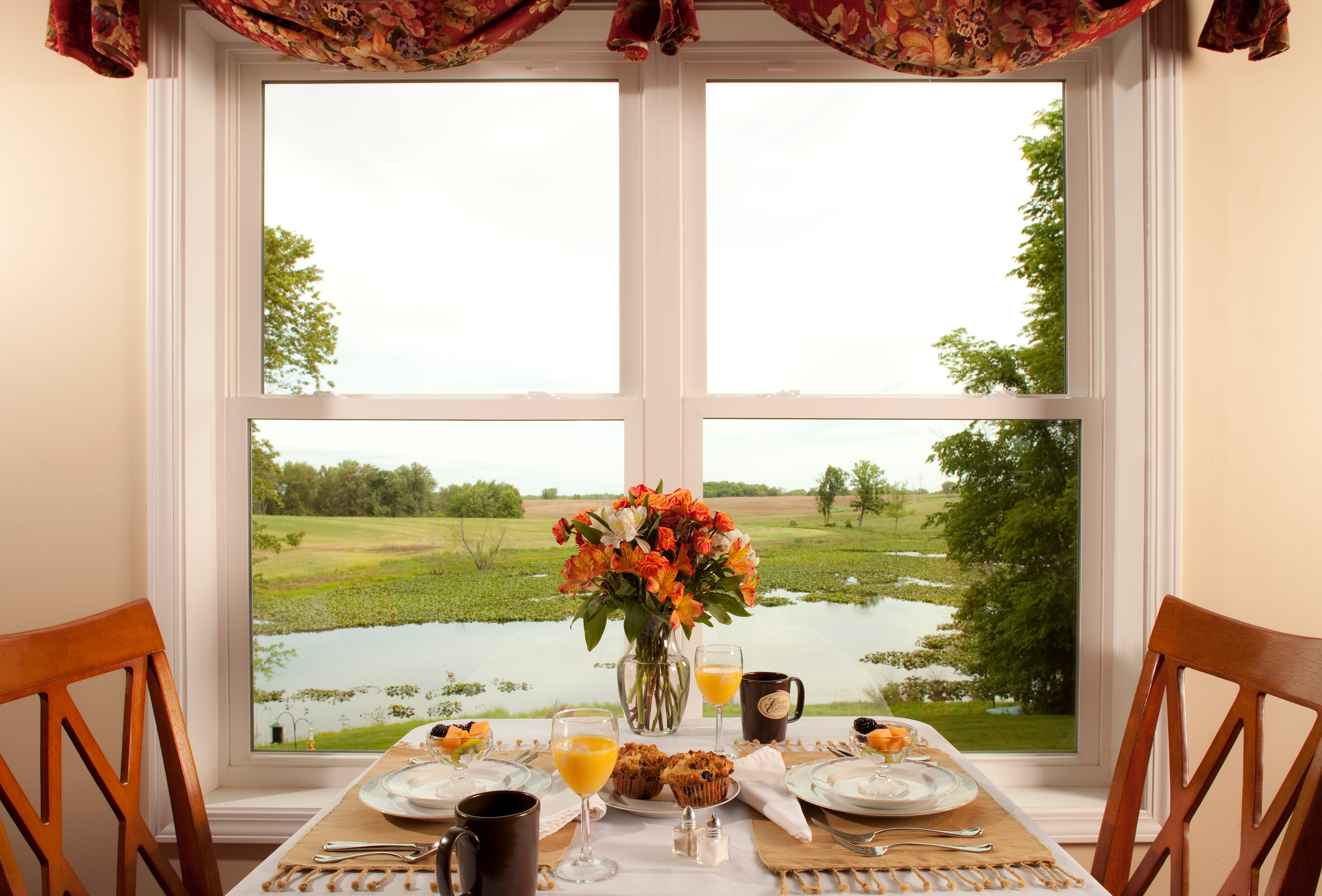 Table set with white plates, muffins, coffee, juice, and fresh flowers by a window overlooking the beautiful grounds