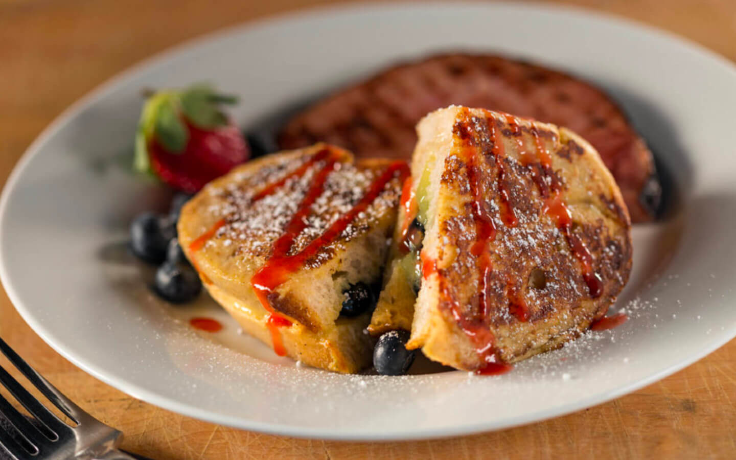 Stuffed french toast on white plate sprinkled with powdered sugar and strawberry sauce blueberries and strawberries