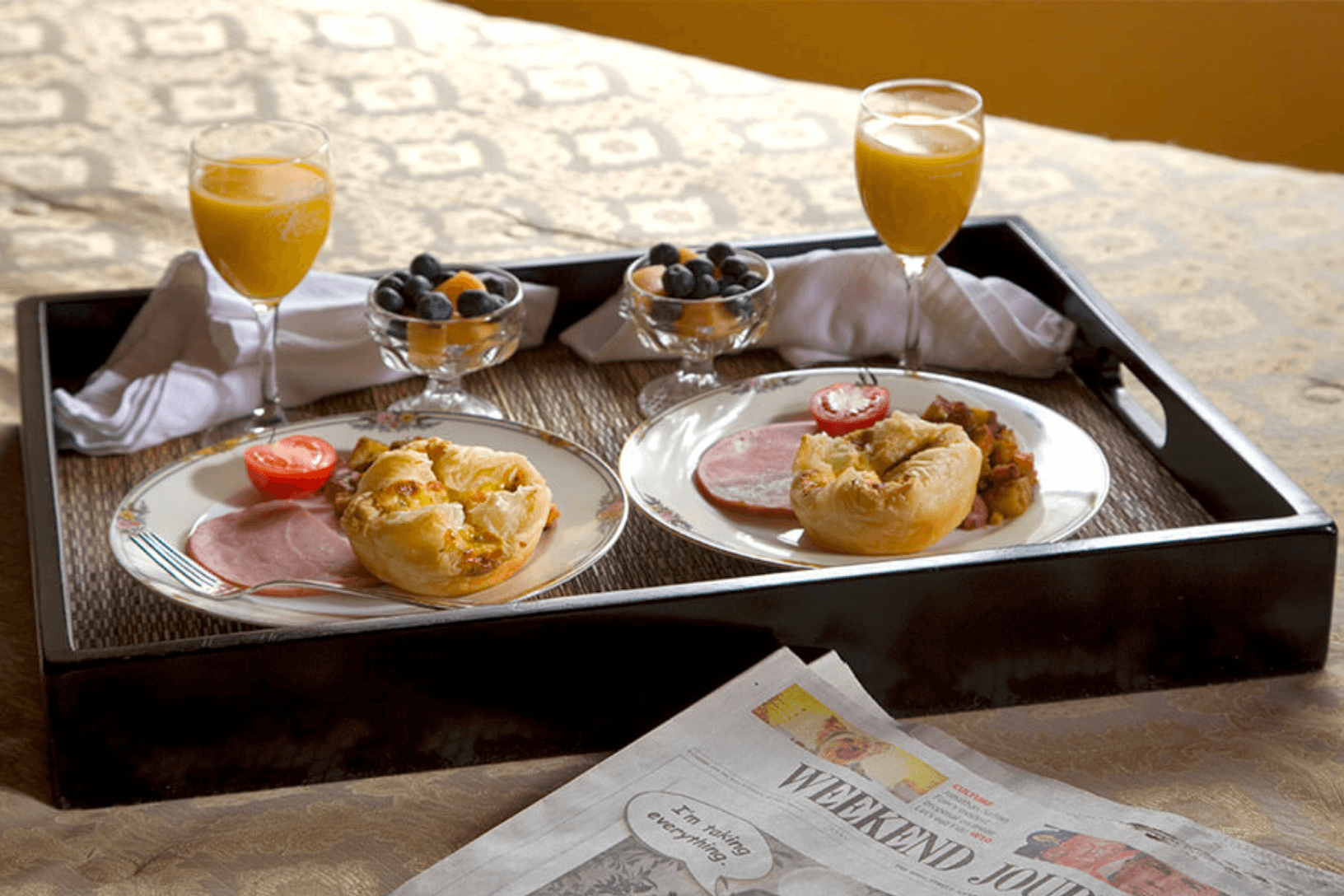 Breakfast tray sitting on the bed topped with sweet and savory breakfast foods and fresh orange juice.