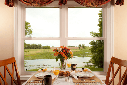 table with chairs set for breakfast by window with open drapes