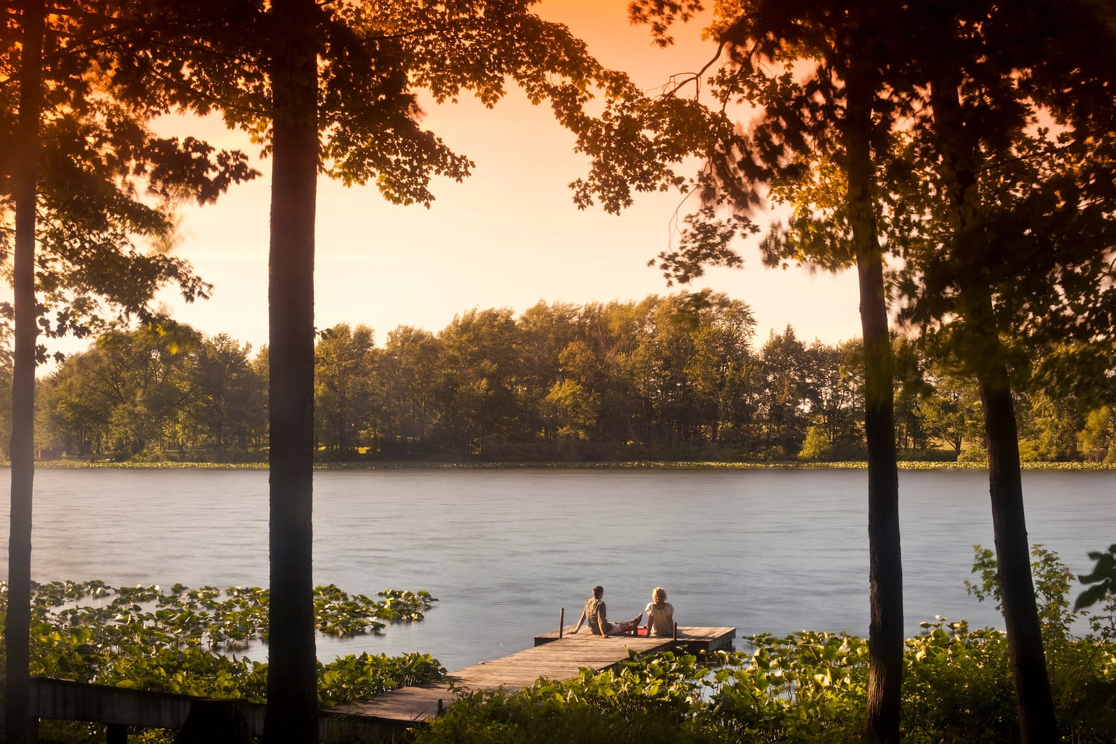 Couple sitting on the end of the dock watching the sunset over the lake