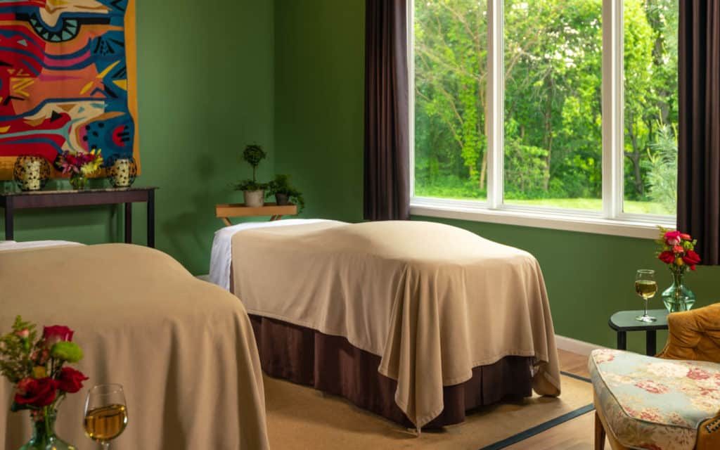 Two massage tables side by side in the spa room with green walls, artwork, and window