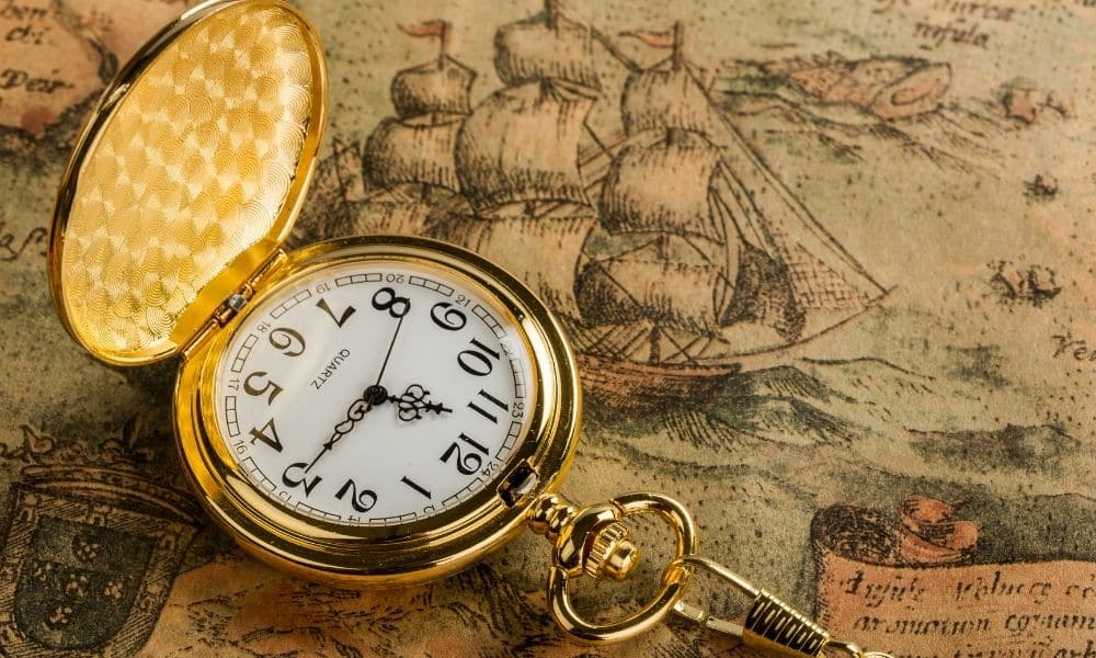 Antique pocket watch propped open on an antique drawing of a ship