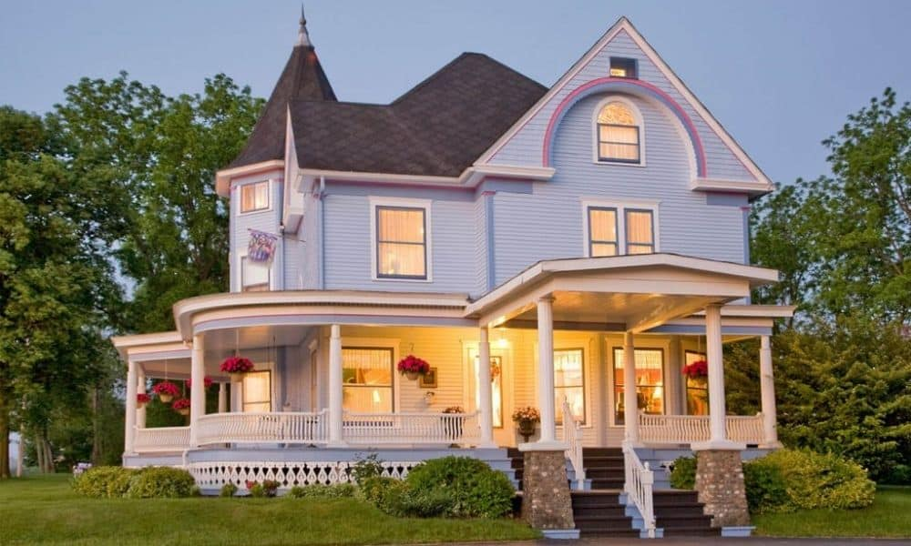 Exterior view of Castle in the Country B&B at dusk, 2-story Victorian home with lights on