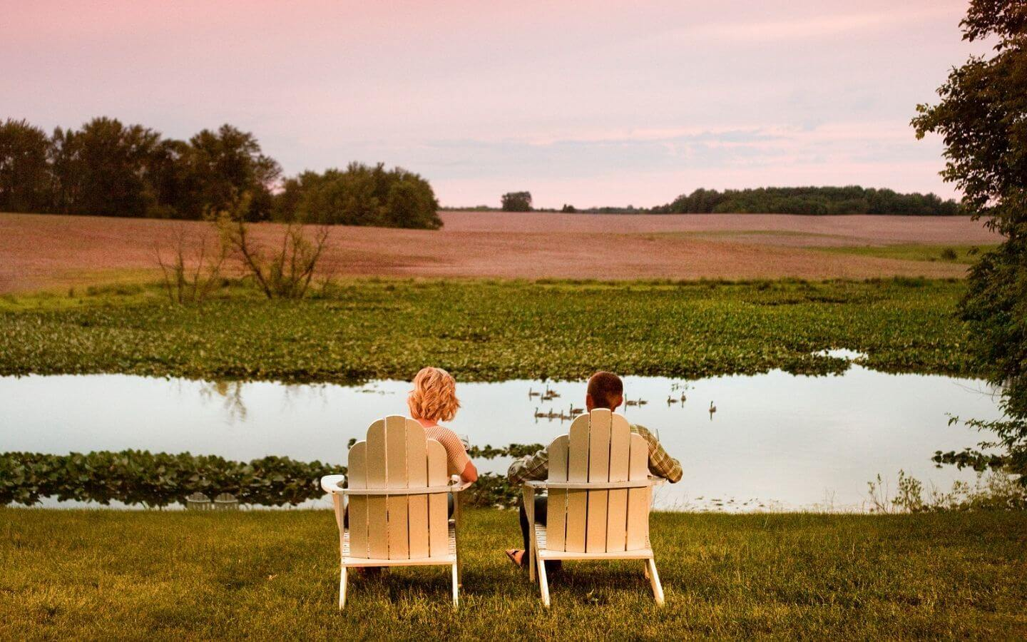 Couple sitting in Adirondack chairs in front of the lake at sunset