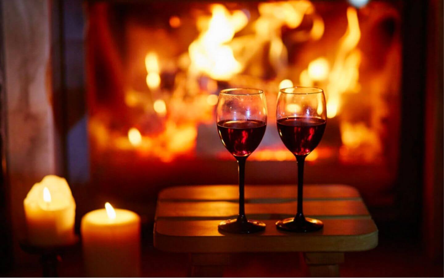 Lit candles and two wine glasses with red wine in front of a glowing fireplace